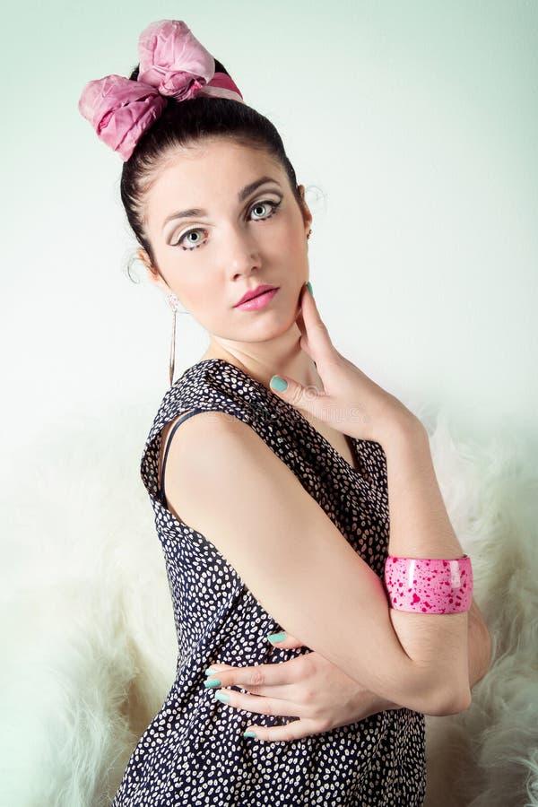 Het mooie meisje in het beeld retro met een roze boog met mooie make-up zit op een stoel in de Studio op een blauwe achtergrond stock foto