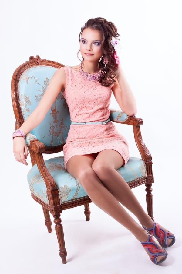 Het mooie meisje in het de Lentebeeld zit op een stoel in barokke st royalty-vrije stock foto