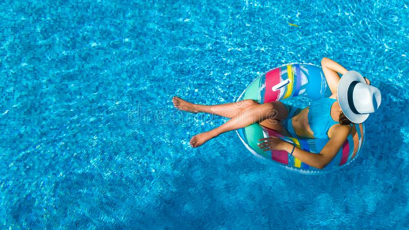 Het mooie meisje in hoed in zwembad lucht hoogste mening van hierboven, vrouw ontspant en zwemt op opblaasbare ringsdoughnut en h stock fotografie