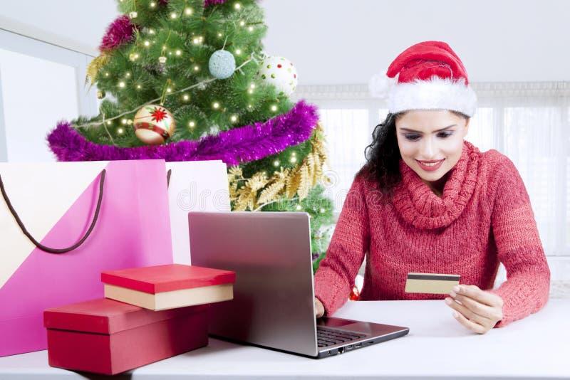 Het mooie meisje houdt creditcard dichtbij Kerstboom stock foto