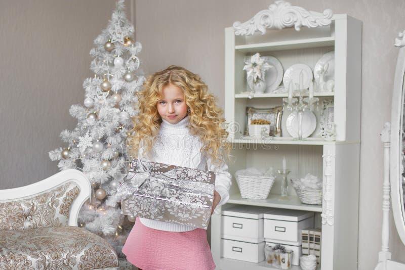 Het mooie meisje houdt een giftdoos bij een lichte nieuwe studio van de jaardecoratie indient royalty-vrije stock fotografie