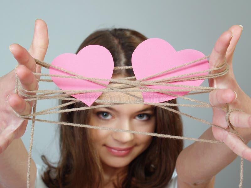 Het mooie meisje houdt twee roze harten in haar handen royalty-vrije stock afbeelding