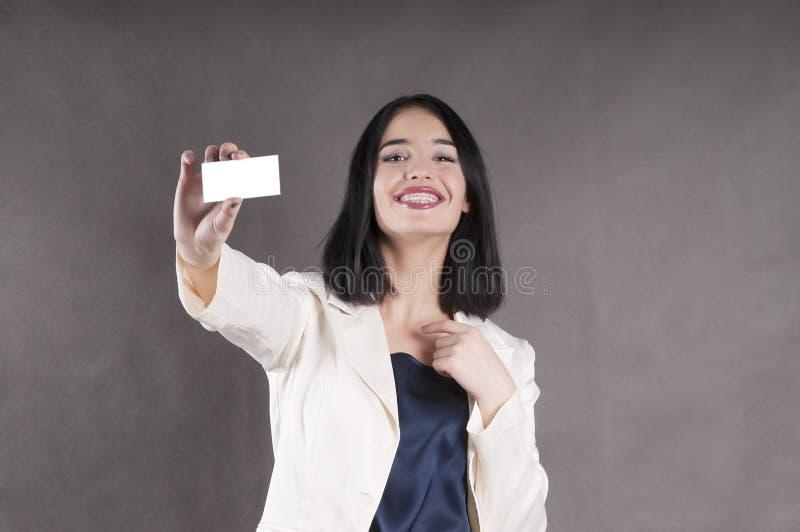 Het mooie meisje houdt uitdeelt adreskaartjestudio marketing steunen stock afbeeldingen