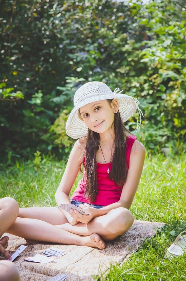 Het mooie meisje 10 jaar oud in een witte hoedenzitting op het gras in de zomer tuiniert royalty-vrije stock foto