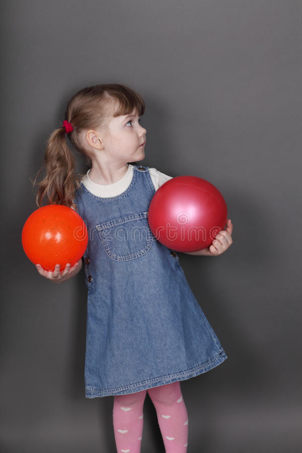 Het mooie meisje in jeanskleding houdt twee ballen stock afbeelding
