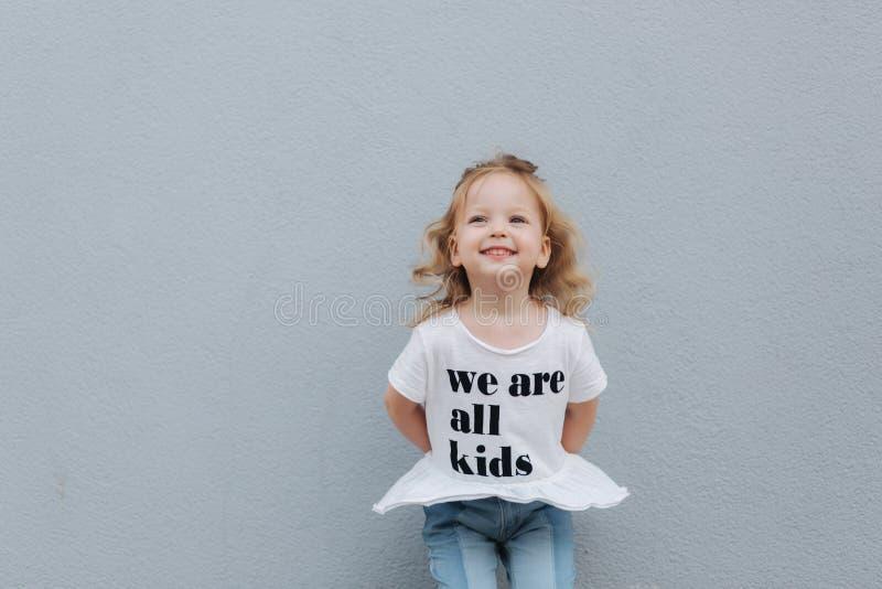 Het mooie meisje kleedde zich in wit overhemd en de jeans bevinden zich voor grijze muur Gelukkige kinderen royalty-vrije stock afbeeldingen