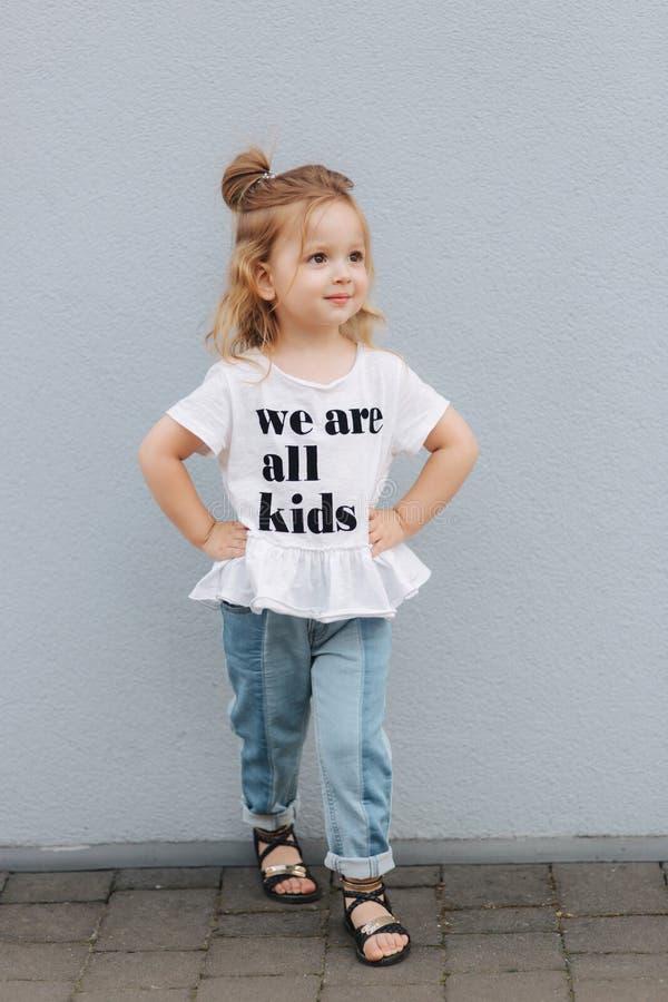 Het mooie meisje kleedde zich in wit overhemd en de jeans bevinden zich voor grijze muur Gelukkige kinderen stock foto's