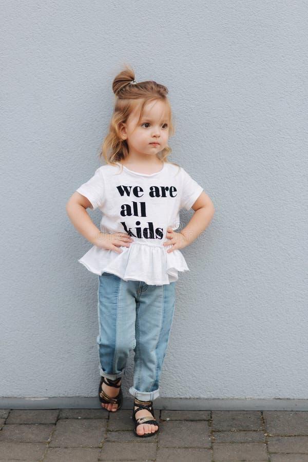 Het mooie meisje kleedde zich in wit overhemd en de jeans bevinden zich voor grijze muur Gelukkige kinderen royalty-vrije stock afbeelding