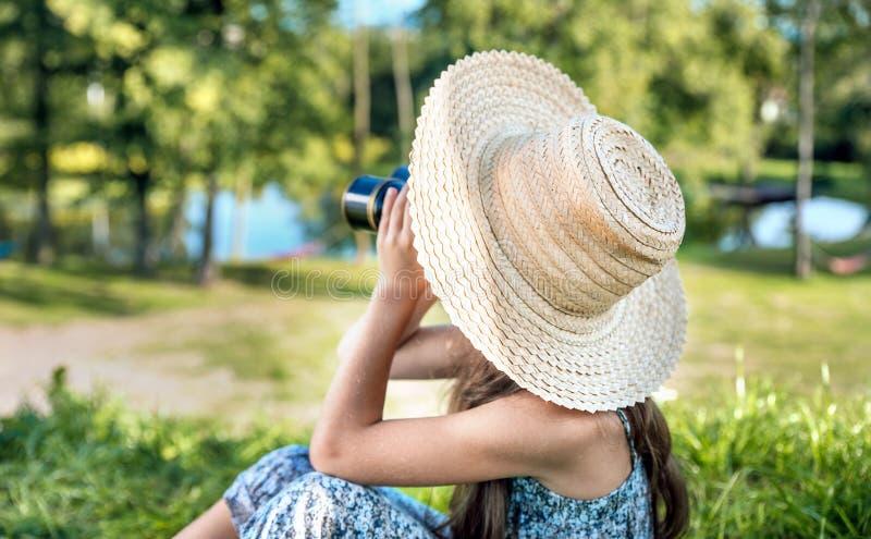 Het mooie meisje letten op met de verrekijkers royalty-vrije stock foto's