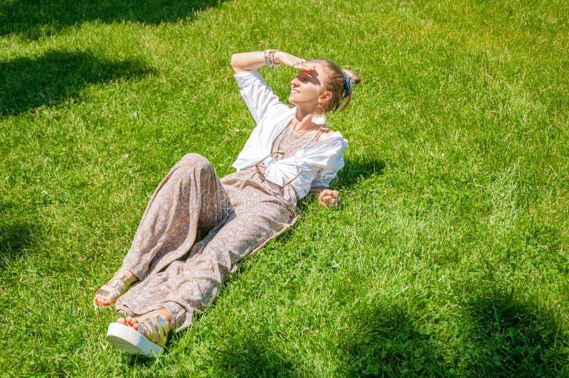 Het mooie meisje liggen op groen gras en de glimlach genieten van zonnige dag in park Het concept van de zomer stock foto