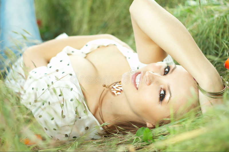 Het mooie meisje liggen van gras royalty-vrije stock foto's