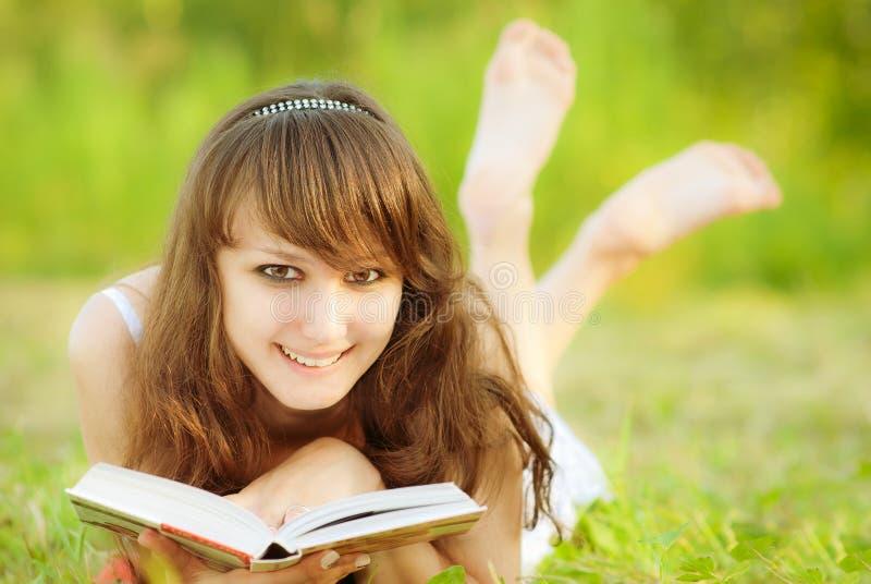 Het mooie meisje ligt en leest stock fotografie