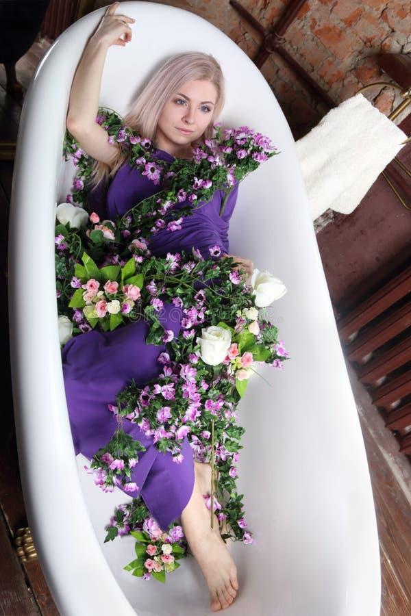 Het mooie meisje in lilac kleding ligt in bad met bloemen royalty-vrije stock afbeeldingen