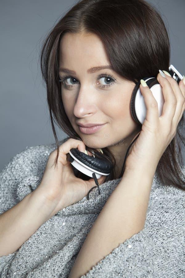 Het mooie meisje luistert aan muziek stock afbeelding