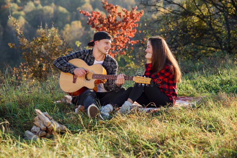 Het mooie meisje luistert de muziek van haar vriend die spelend op de gitaar Gelukkig paar met gitaar die op picknick binnen rust stock afbeelding