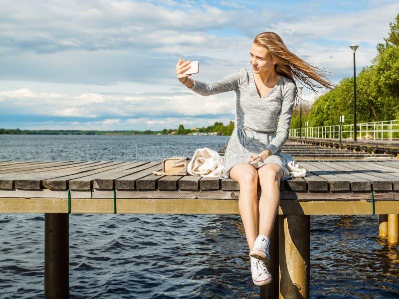 Het mooie meisje maakt selfie Al alleen, zit zij op een rivierpijler, spreidt de wind blond haar in verschillende richtingen uit royalty-vrije stock foto