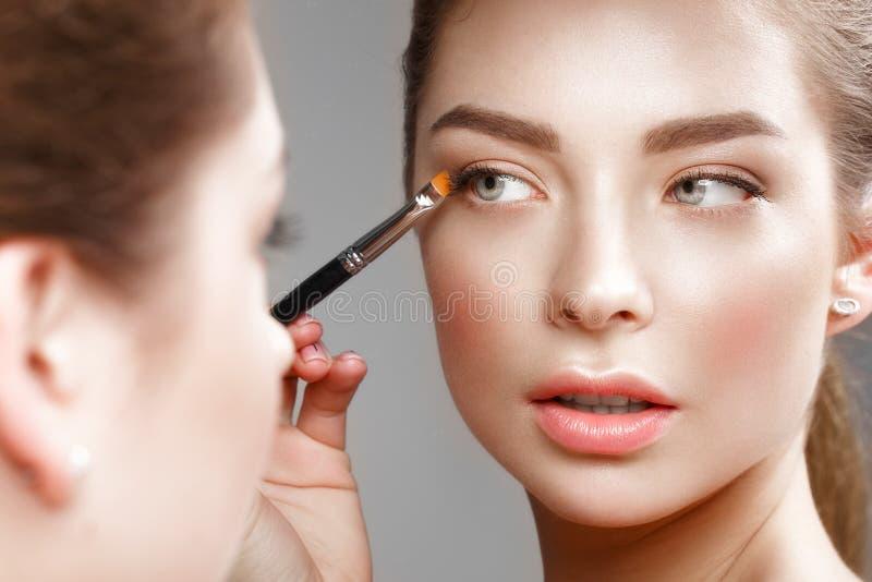 Het mooie meisje maakt zich een samenstelling in de spiegel Het Gezicht van de schoonheid stock afbeeldingen