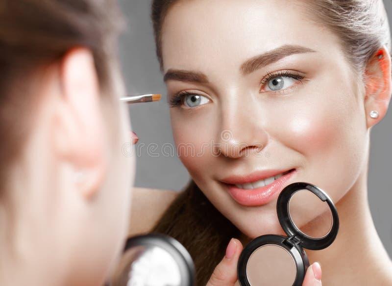 Het mooie meisje maakt zich een samenstelling in de spiegel Het Gezicht van de schoonheid stock afbeelding