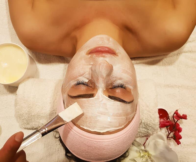 Het mooie meisje, maskeert kosmetische skincareschoonheidsspecialist gezond in de de vochtinbrengende crème skincare kosmetiek va stock afbeeldingen