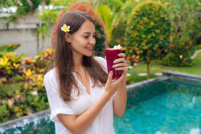 Het mooie meisje met bloem in haar haar en glazen draakfruit smoothie bevindt zich in tropische tuin royalty-vrije stock afbeeldingen