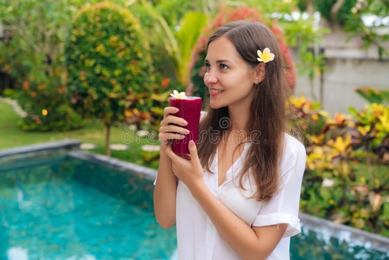 Het mooie meisje met bloem in haar haar en glazen vers sap bevindt zich in tropische tuin royalty-vrije stock foto's