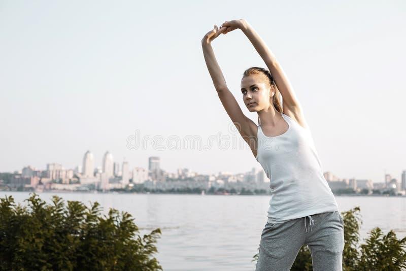 Het Mooie meisje met blond haar die oefening op stadsachtergrond doen stock afbeeldingen