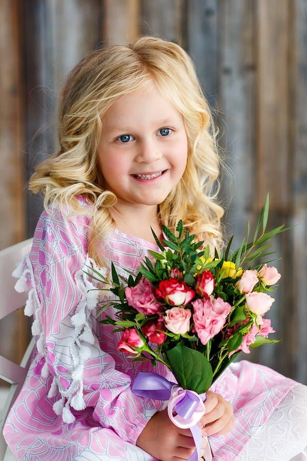 Het mooie meisje met blond haar en een boeket van verse bloemen zit en glimlacht in een heldere studio Daglicht stock foto