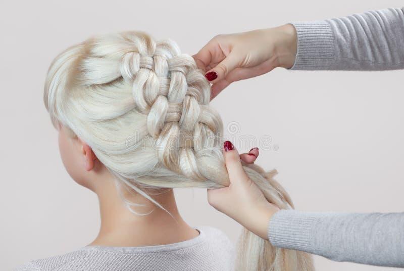 Het mooie meisje met blondehaar, kapper weeft een vlechtclose-up stock afbeelding