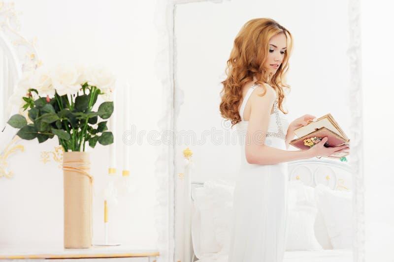 Het mooie meisje met bruin lang haar bevindt zich dichtbij een spiegel houdend een album met foto's in haar handen Portret van jo stock afbeelding