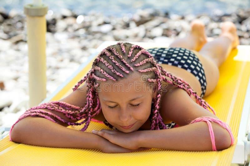 Het mooie meisje met de roze slaap van het dreadlockskapsel sunbed onder parasol in strand royalty-vrije stock afbeelding