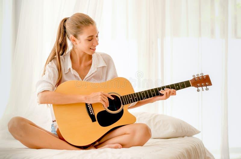 Het mooie meisje met de witte gitaar van het overhemdsspel op bed en kijkt gelukkig met het glimlachen royalty-vrije stock foto's