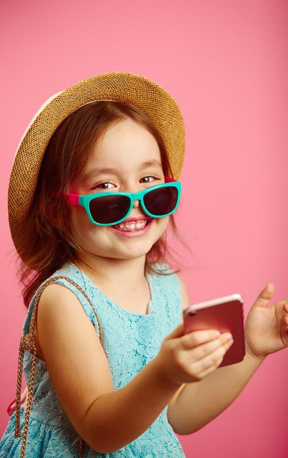 Het mooie meisje met een charmante glimlach, kleedde zich in strohoed en zonnebril, bekijkend de camera, houdend een telefoon royalty-vrije stock foto