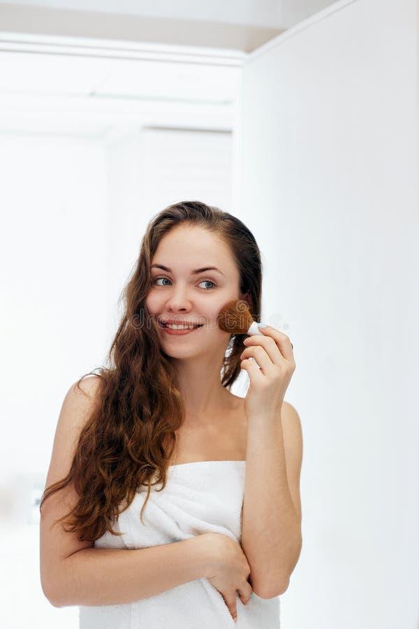Het mooie meisje met kosmetische poederborstel voor maakt omhoog makeup Samenstelling die voor perfecte huid van toepassing zijn royalty-vrije stock afbeeldingen