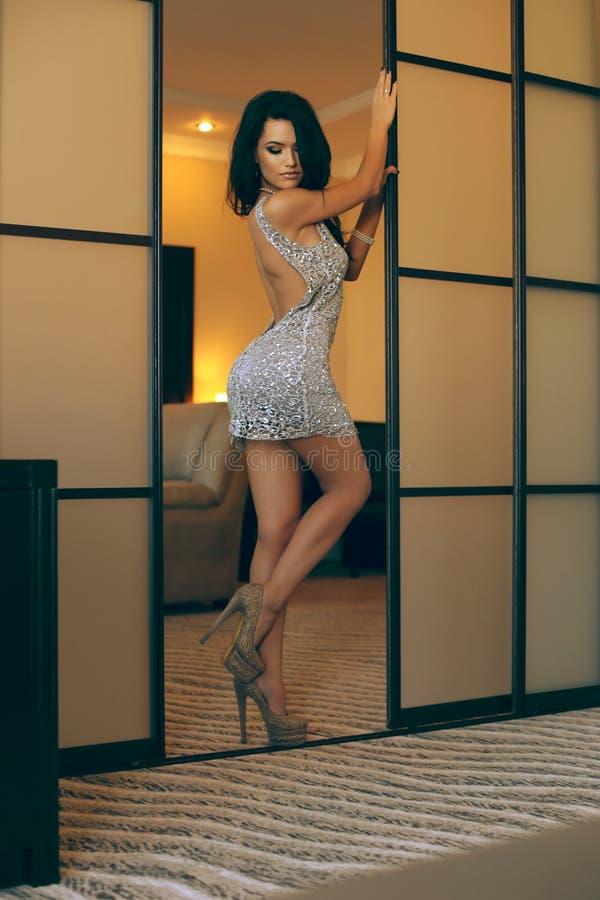 Het mooie meisje met lang donker haar draagt elegante kleding en toebehoren stock foto