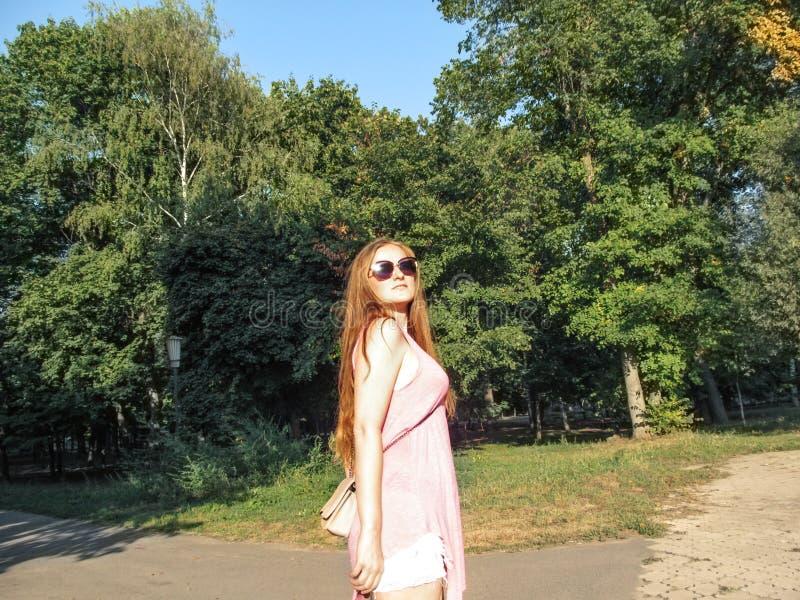 Het mooie meisje met lang gouden haar in zonnebril bekijkt de zon Jonge vrouw die in roze kleren in een park op duidelijk lopen royalty-vrije stock fotografie