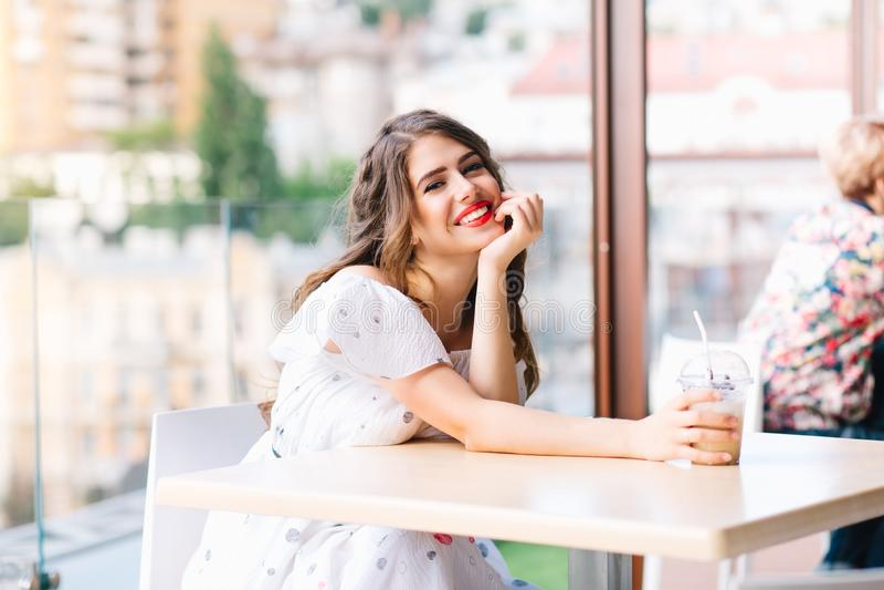 Het mooie meisje met lang haar sittting bij lijst aangaande het terras in koffie Zij draagt een witte kleding met naakte schouder stock afbeeldingen