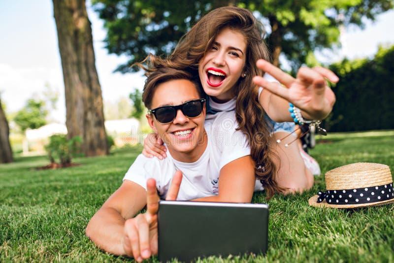 Het mooie meisje met lang krullend haar en rode lippen ligt op rug van knappe kerel in zonnebril op gras in de zomerpark stock foto's