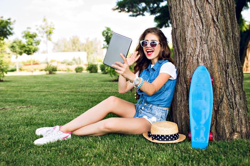 Het mooie meisje met lang krullend haar zit dichtbij boom in de zomerpark Zij draagt jeansborrels, buis, zonnebril Zij is stock foto's