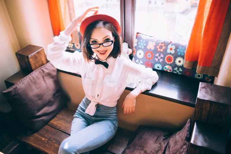 Het mooie meisje met rode hoed zit op een bank royalty-vrije stock afbeeldingen