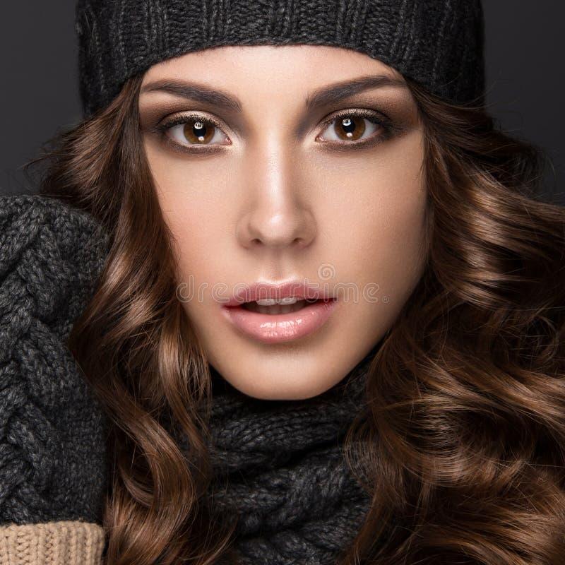 Het mooie meisje met Smokeymakeup, krullen in zwarte breit hoed Warm de winterbeeld Het Gezicht van de schoonheid stock foto