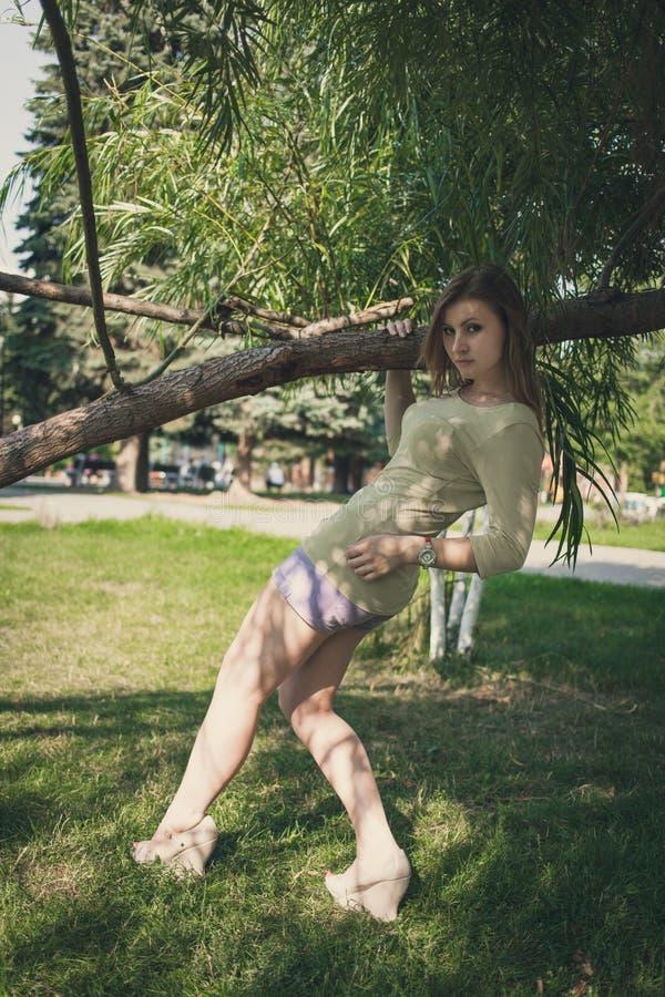 Het mooie meisje met stromend haar in korte borrels die zich in gebogen bevinden stelt dichtbij een boom op een achtergrond van g stock afbeeldingen