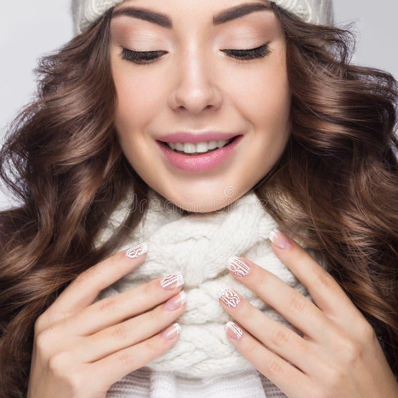 Het mooie meisje met zachte make-up, de ontwerpmanicure en de glimlach in wit breien hoed Warm de winterbeeld Het Gezicht van de  royalty-vrije stock fotografie