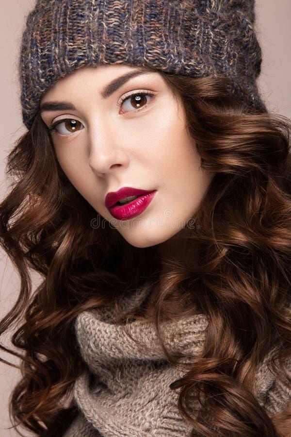 Het mooie meisje met zachte make-up, krullen in bruin breit hoed Warm de winterbeeld Het Gezicht van de schoonheid royalty-vrije stock foto
