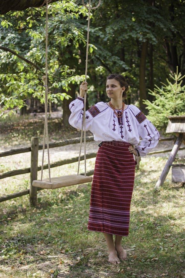 Het mooie meisje in Oekraïense nationale kleding bevindt zich dichtbij de schommeling royalty-vrije stock foto's