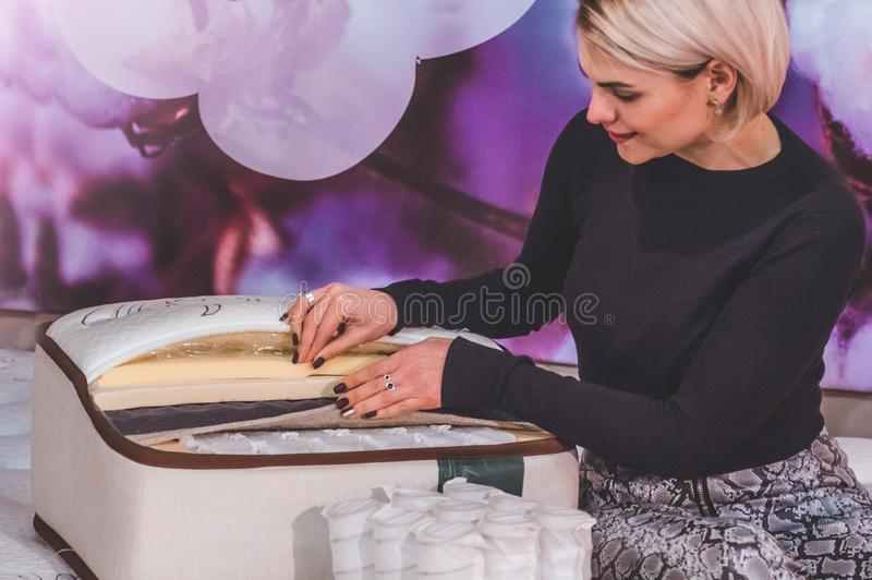 Het mooie meisje onderzoekt de vuller voor de matras Kokosnotencoir, het latexrubber van Aardparagraaf, de onafhankelijke lente v royalty-vrije stock afbeeldingen