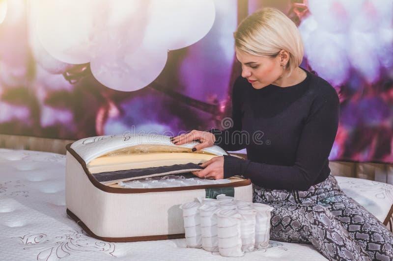 Het mooie meisje onderzoekt de vuller voor de matras Kokosnotencoir, het latexrubber van Aardparagraaf, de onafhankelijke lente v royalty-vrije stock afbeelding