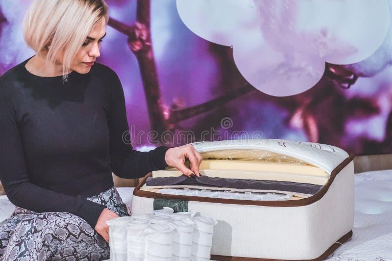 Het mooie meisje onderzoekt de vuller voor de matras Kokosnotencoir, het latexrubber van Aardparagraaf, de onafhankelijke lente v royalty-vrije stock foto's
