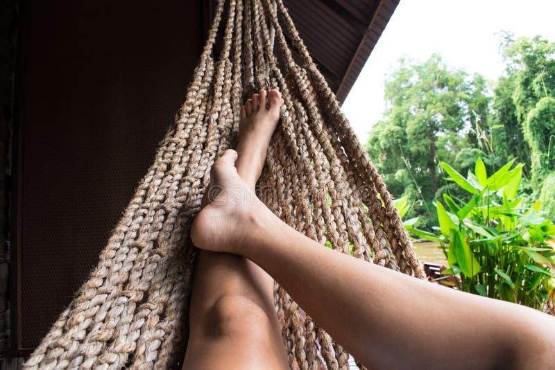 Het mooie meisje ontspannen in een hangmat thuis royalty-vrije stock afbeelding