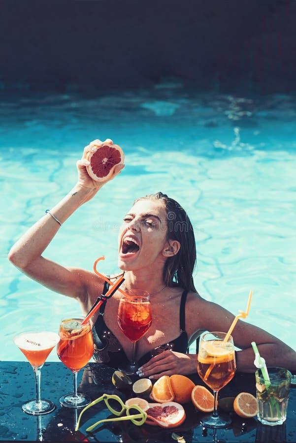 Het mooie meisje ontspannen op het strand met cocktail stock afbeeldingen