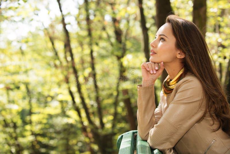 Het mooie meisje ontspant en rust in de herfstpark royalty-vrije stock afbeeldingen